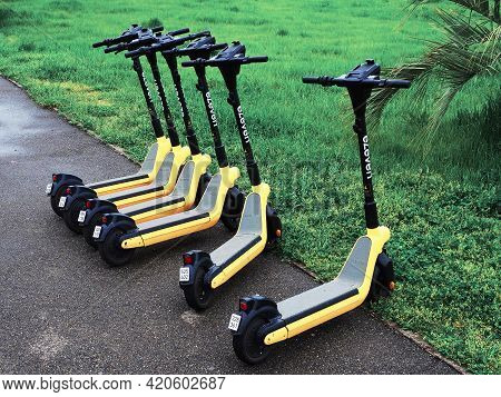 Russia, Sochi 16.04.2021. Several Black And Yellow Electric Scooters Are Parked On The Asphalt Along
