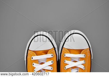 Two Yellow Womens Fabric Sneakers On Grey Background. Colors Of The Year 2021. Stylish Youth Comfort