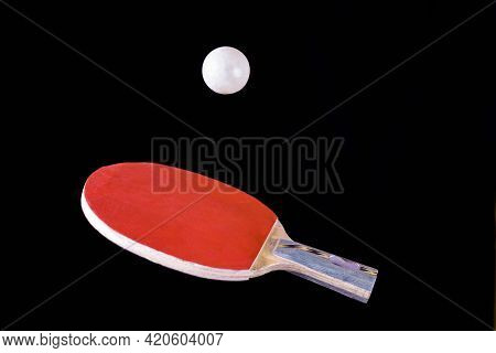 Red Ping Pong Racket At The Moment Of Throwing The Ball. A Red Ping Pong Racket With A White Ball On