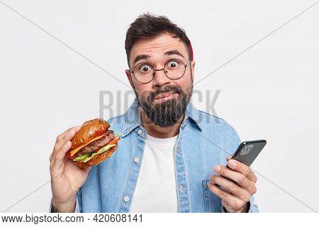 Hesitant Embarrassed Bearded Man Holds Tasty Hamburger Checks Newsfeed Via Smartphone Eats Fast Food