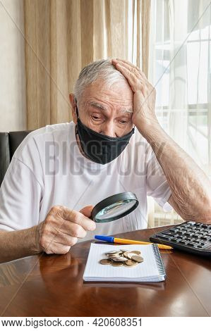 Old Man In A Medical Mask With A Magnifying Glass Examines And Counts Pennies From The Pension Fund.