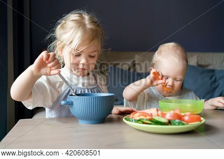 Two Small Cute Kids Older Sister And Baby Boy Brother Having Healthy Lunch, Eating Soup And Fresh Ve