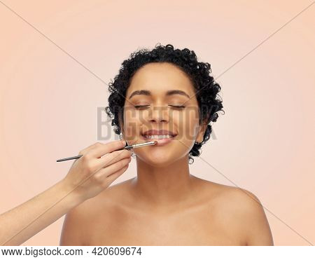 beauty, cosmetics and people concept - beautiful young african american woman and hand of make up artist with brush applying lipstick or lip gloss over beige background