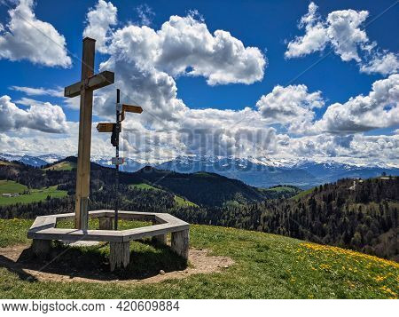 Summit Cross On The Hill With Lots Of Beautiful Dandelion Flowers. Huettchopf In The Zurich Oberland