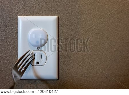 Selective Focus On Edge Of A Metal Fork About To Be Inserted Into An Open Electrical Outlet Socket.