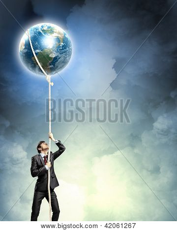 Image of businessman climbing rope attached to earth planet poster