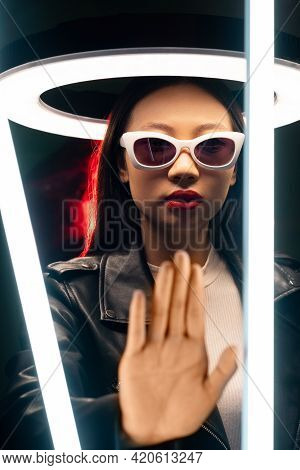 Stop Gesture. Cyberpunk Portrait. Future Warning. Red Neon Color Light Mysterious Asian Girl In Glas