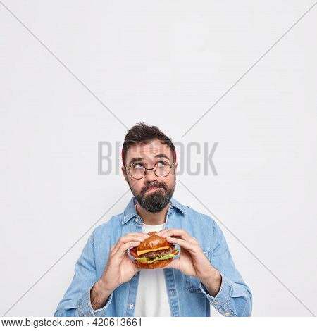 Vertical Shot Of Pensive Bearded Man Holds Appetizing Hamburger Focused Above Thinks Deeply About So