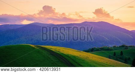 Rolling Rural Mountain Landscape At Dusk. Gorgeous Nature Scenery In Spring. Clouds On The Sky In Ev