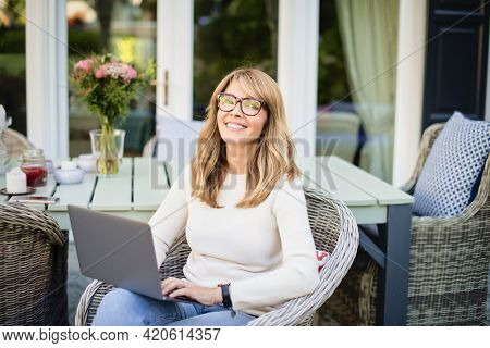 Attractive Cheerful Woman Using Laptop While Sitting In The Balcony At Home