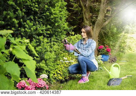 Smiling Young Woman Gardening In The Backyard At Home