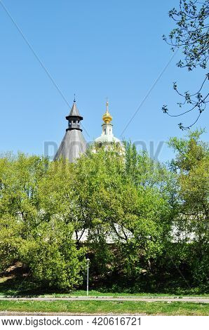 The Golden Dome Of The Bell Tower And The Gray Roof Of The Monastery Tower On A Blue Background. Vie