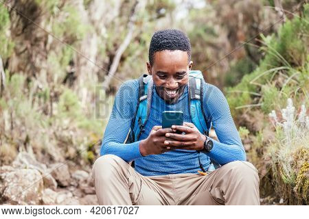 Young African Ethnicity Man Video Chatting Via Cellphone With Somebody And Cheerfully Laughing As He