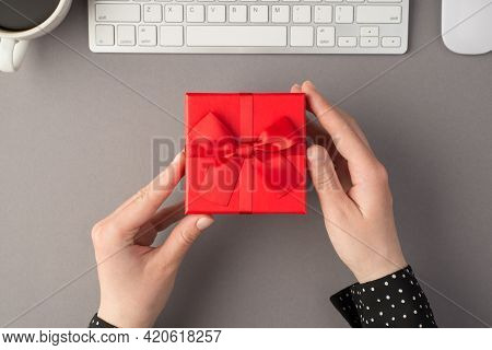 First Person Top View Photo Of Female Hands Holding Red Giftbox With Ribbon Bow White Keyboard Mouse