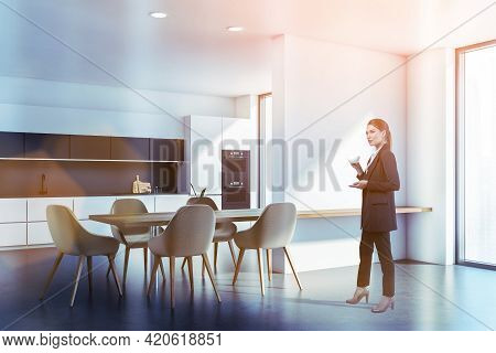 Attractive Woman At Kitchen Room With Furniture Wearing Formal Suit And Drinking Coffee, Lens Flare.