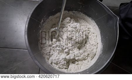 Worker Mixing Plaster In A Bucket For Alignment And Putty Walls Of The Apartment Using An Electric D