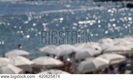 Blurred Seascape With Defocused White Beach Umbrellas And Sunshades Against Blur Blue Sea Water With