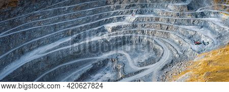 Wide Panorama Of Open Pit Stone Quarry With Terraces, Excavator And Stone Crusher Machines