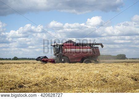 26.07.2020 Russia, Bryansk Region. Red Harvester In The Summer Field Harvests. Combine Harvester Agr
