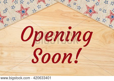 Opening Soon Wood Sign With Blue And Red Stars Ribbon