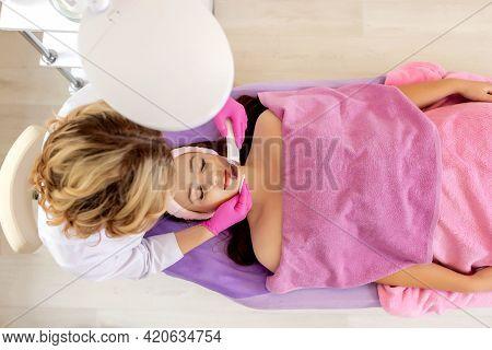 Ultrasonic Scrabbing. Young Woman Receiving Ultrasound Cavitation Facial Peeling Cleansing. Cosmetol