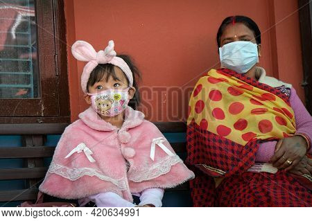 Kathmandu, Nepal, 16 March 2020: Mother And Child Wearing Protecting Face Masks Waiting For Health C