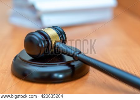 The Judge's Black Hammer Lies On A Light Table Against The Background Of Cases. Beautiful Bokeh