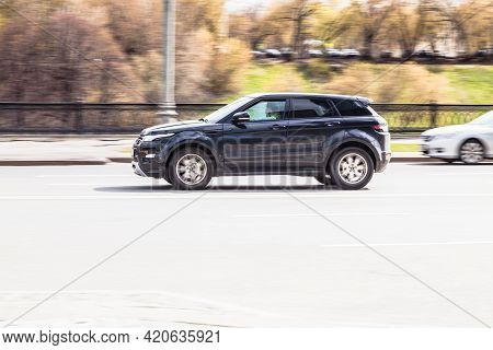 Land Rover Range Rover Evoque Rides On The City Road. Black Compact Suv Driving Along The Street In