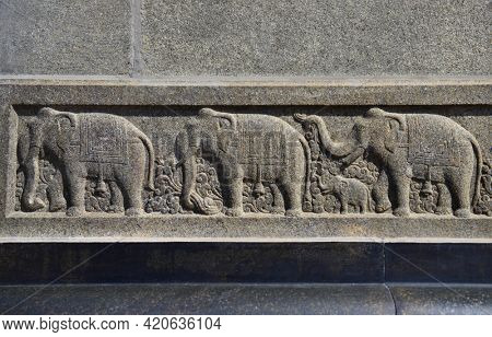 Beautifully carved elephant figures on the stone from an ancient Indian temple. Embossed figures of elephants in the row intricately carved from black stone.