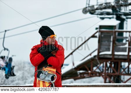 Male Snowboarder In A Red Suit Walking On The Snowy Hill With Snowboard, Skiing And Snowboarding Con