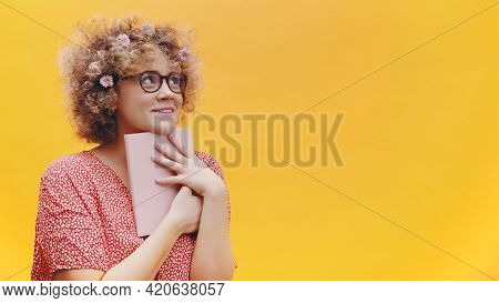 Excited Young Woman Student Or Writer Holding Book And Thinking. Curly Hair Full Of Spring Flowers.