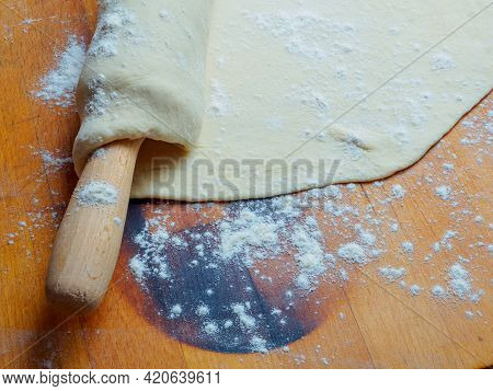 Pizza Dough Base Wrapped On A Rolling Pin On A Wooden Table Sprinkled With Flour. Rolling Out Thin P