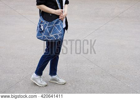 Part Of The Body Of Woman In Denim Trousers And Sneakers, Which Keeps Bag Made Of Denim Tissue On He