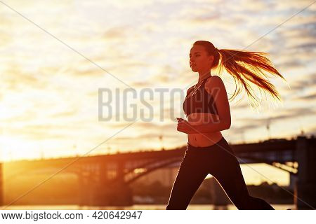 Running Woman In The Sand At Sunrise. Morning Jogging On The Beach Or Coast Of River On Bridge Urban