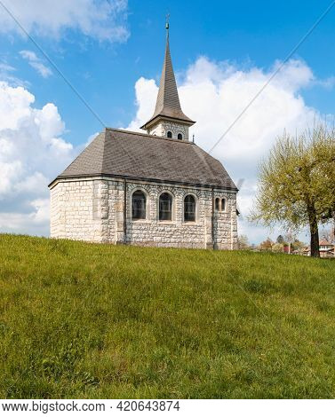 Characteristic church in the green field in the Swiss Alps of the Canton Jura. Nobody inside. Cloudy day.