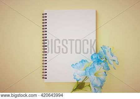 Spiral Notebook Or Spring Notebook In Unlined Type And Blue Flower On Pastel Yellow Minimalist Backg
