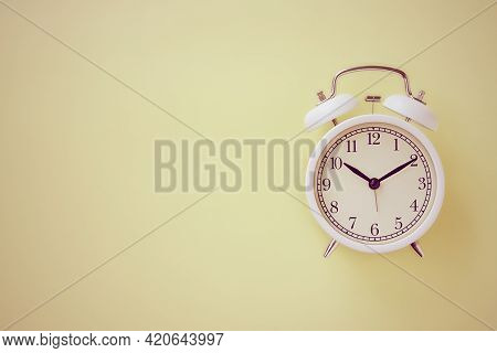 White Alarm Clock On Pastel Yellow Minimalist Background On Right Frame In Vintage Tone