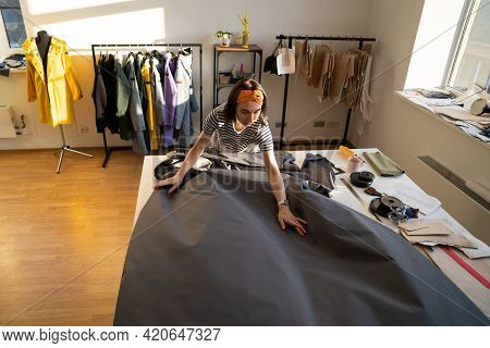 Dressmaker Unrolling Dress Fabric On Atelier Table. Fashion Designer Tailor Or Sewer In Fashion Stud