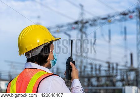 Female Engineers Work Through Radio Communication In The Area Of high Voltage Station By Wear A Ma