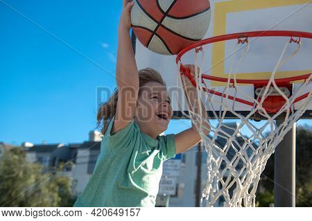 Basketball Child Player Running Up And Dunking The Ball. Active Kid Enjoying Outdoor Game With Baske