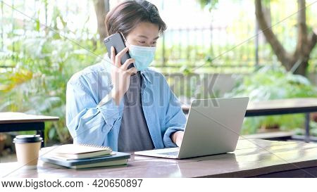 Young Asian Campus Student Man Wearing Protection Mask Talking Moblie Phone And Working With Laptop