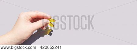 Omega3 Gel Capsule In Hand. Sun Shadow. Yellow Vitamin. Health Eating. Dietology Drug. Fish Oil Supp