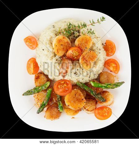 Risotto with pan seared sea scallops isolated on black background