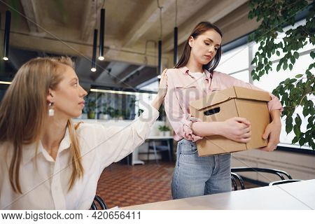Young Businesswoman Holding Box Of Personal Belongings About To Leave Office After Quitting Job