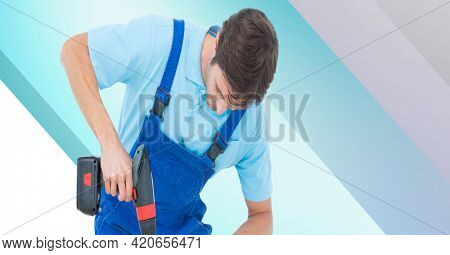 Caucasian handy man using drill on blue and white stripes. diy and home decoration concept digitally generated image.