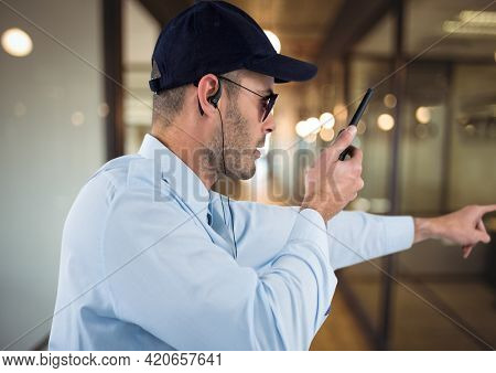 Composition of male security guard using walkie talkie holding hand out over blurred background. security and safety concept digitally generated image.