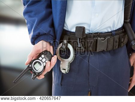 Composition of midsection of male security guard holding walkie talkie over blurred background. security and safety concept digitally generated image.