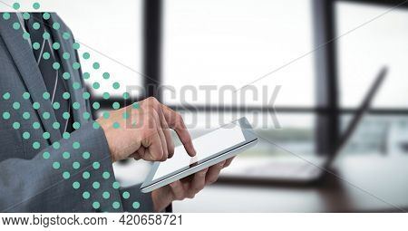 Composition of green dots and midsection of businessman using tablet over modern interiors. global business and technology concept digitally generated image.