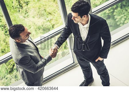 Businessman Handshake With Another Businessman Partner In Modern Workplace Office. People Corporate