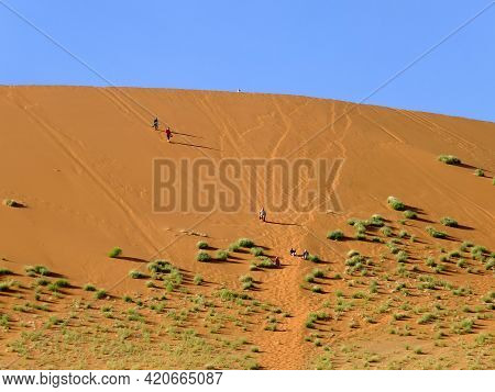 Sossusvlei, Namibia - 02 May 2012: People In Dunes, Namib Desert, Sossusvlei, Namibia